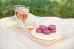 Ανοικτό ροζ και φούξια ρόδινα γαλλικά macaroons ή macaroons με goblets γυαλιού του ρόδινου κρασιού σε ένα στρογγυλό άσπρο πιάτο σ στοκ εικόνες