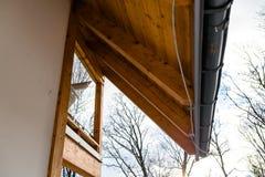 Ανοικτό ροζ πρόσοψη σπιτιών με ορατές ξύλινες soffit και την υδρορροή στεγών Δέντρα στο υπόβαθρο στοκ εικόνες με δικαίωμα ελεύθερης χρήσης