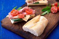 Ανοικτό σάντουιτς με το jamon, arugula, ντομάτες, τυρί στο ξύλινο μπλε υπόβαθρο πινάκων αγροτικός Στοκ Φωτογραφίες
