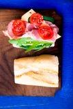 Ανοικτό σάντουιτς με το jamon, arugula, ντομάτες, τυρί στο ξύλινο μπλε υπόβαθρο πινάκων αγροτικός Τοπ όψη Στοκ Φωτογραφίες