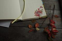 Ανοικτό σημειωματάριο με τα υπόλοιπα αυτοκόλλητων ετικεττών φθινοπώρου σε ένα ξύλινο υπόβαθρο Στοκ Εικόνες