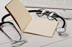 Ανοικτό σημειωματάριο με τις κενές σελίδες με ένα στηθοσκόπιο Στοκ Φωτογραφία