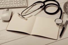 Ανοικτό σημειωματάριο με τις κενές σελίδες με το στηθοσκόπιο Στοκ Φωτογραφίες