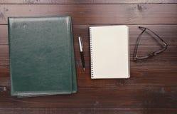 Ανοικτό σημειωματάριο με τις κενές σελίδες, τη μάνδρα, το φάκελλο δέρματος και τα γυαλιά στοκ εικόνα