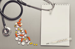 Ανοικτό σημειωματάριο με τις κενές σελίδες, χάπια, κάψες, θερμόμετρο και Στοκ Εικόνες