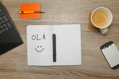 Ανοικτό σημειωματάριο με τις πορτογαλικές λέξεις ` OLA ` γειά σου και ένα φλιτζάνι του καφέ στο ξύλινο υπόβαθρο Στοκ εικόνα με δικαίωμα ελεύθερης χρήσης