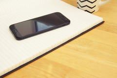 Ανοικτό σημειωματάριο με το φλιτζάνι του καφέ στο ξύλινο γραφείο διάστημα αντιγράφων στοκ φωτογραφίες με δικαίωμα ελεύθερης χρήσης