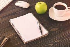 Ανοικτό σημειωματάριο στον υπολογιστή γραφείου γραφείων με το φλιτζάνι του καφέ Στοκ Εικόνα