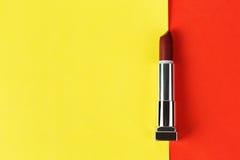 Ανοικτό σκούρο κόκκινο κραγιόν στο κόκκινο και κίτρινο υπόβαθρο Στοκ Εικόνες