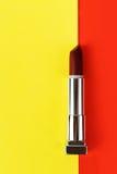 Ανοικτό σκούρο κόκκινο κραγιόν στο κόκκινο και κίτρινο υπόβαθρο Στοκ φωτογραφία με δικαίωμα ελεύθερης χρήσης