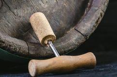 Ανοιχτήρι δίπλα σε ένα ξύλινο βαρέλι κρασιού Κρασί σε ένα ξύλινο βαρέλι Μμένο, μαύρο ξύλινο υπόβαθρο Τρύγος Copyspace για ένα κεί Στοκ εικόνα με δικαίωμα ελεύθερης χρήσης