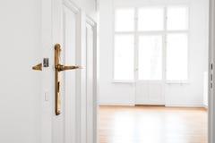 Ανοιχτή πόρτα, κενό δωμάτιο στο ανακαινισμένο παλαιό επίπεδο στοκ εικόνα
