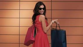 Ανοιχτόχρωμης επιδερμίδας όμορφες περιστροφές γυναικών γύρω με τις τσάντες αγορών της απόθεμα βίντεο