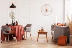 Ανοιχτό να δειπνήσει χώρου και περιοχή διαβίωσης με τον γκρίζους Σκανδιναβικούς καναπέ και τον πίνακα με τις καρέκλες στοκ εικόνες