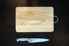 Ανοξείδωτο μαχαίρι κουζινών και ξύλινος τέμνων πίνακας Στοκ εικόνα με δικαίωμα ελεύθερης χρήσης