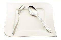 Ανοξείδωτα δίκρανο και κουτάλι στο πιάτο Στοκ Εικόνες