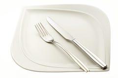 Ανοξείδωτα δίκρανο και μαχαίρι στο πιάτο Στοκ Φωτογραφία