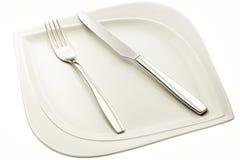 Ανοξείδωτα δίκρανο και μαχαίρι στο πιάτο Στοκ φωτογραφίες με δικαίωμα ελεύθερης χρήσης
