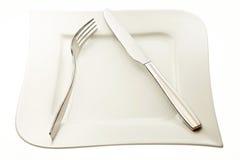 Ανοξείδωτα δίκρανο και μαχαίρι στο πιάτο Στοκ Εικόνες