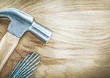 Ανοξείδωτα καρφιά σφυριών νυχιών στην ξύλινη έννοια οικοδόμησης πινάκων Στοκ Εικόνες