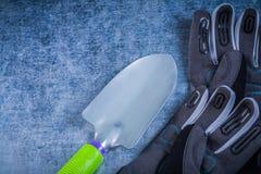 Ανοξείδωτα προστατευτικά γάντια κηπουρικής trowel στο μεταλλικό backgro Στοκ Φωτογραφίες