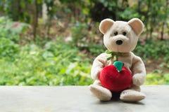 Αντέξτε την κούκλα με το πράσινο υπόβαθρο bokeh Στοκ Φωτογραφία