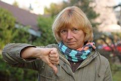 Αντίχειρας κάτω από την ώριμη γυναίκα Στοκ εικόνες με δικαίωμα ελεύθερης χρήσης