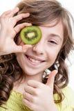 Αντίχειρας κοριτσιών επάνω για τις πράσινες βιταμίνες ακτινίδιων Στοκ Εικόνες