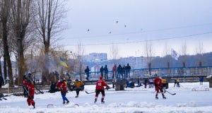 Ανταγωνισμοί χόκεϋ κάτω από το ανοιχτό ουρανό στην καλυμμένη πάγος λίμνη Στοκ Εικόνες