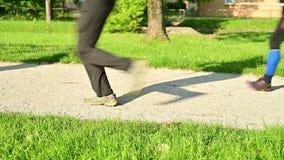 Ανταγωνιστές δρομέων που αρχίζουν έναν υπερβολικό τρέχοντας ανταγωνισμό ιχνών - λεπτομέρεια των ποδιών των δρομέων στην έναρξη εν απόθεμα βίντεο