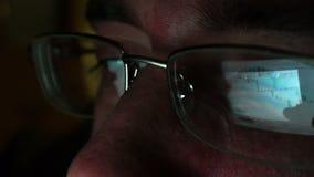 Αντανάκλαση στα γυαλιά των εμπορικών πληροφοριών χρηματιστηρίου από την οθόνη της ταμπλέτας απόθεμα βίντεο