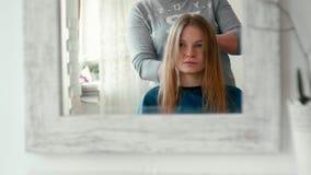 Αντανάκλαση στον καθρέφτη της γυναίκας με τον ψεκασμό στην υγρή τρίχα Hairdressing στο σαλόνι φιλμ μικρού μήκους