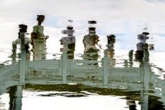 Αντανάκλαση στο νερό των ανθρώπων που στέκονται στη γέφυρα στοκ εικόνες
