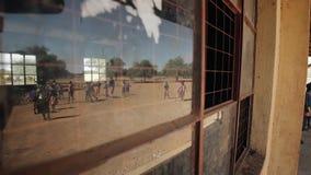 Αντανάκλαση στο παράθυρο Αφρικανικά παιδιά που παίζουν στο αγωνιστικό χώρο ποδοσφαίρου απόθεμα βίντεο