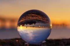 Αντανάκλαση σφαιρών κρυστάλλου στην ακτή στο φως ανατολής Αντανάκλαση μιας γέφυρας στη σφαίρα κρυστάλλου Στοκ Εικόνες