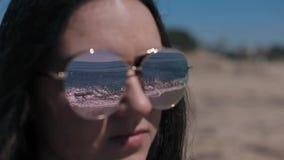 Αντανάκλαση της θάλασσας, των foamy κυμάτων, και της ακτής στα γυαλιά ηλίου ενός νέου όμορφου κοριτσιού φιλμ μικρού μήκους