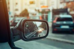 Αντανάκλαση της κυκλοφορίας πόλεων στο δευτερεύοντα καθρέφτη αυτοκινήτων Στοκ Εικόνες