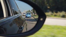 Αντανάκλαση του δρόμου πόλεων στο δευτερεύοντα οπισθοσκόπο καθρέφτη, κανόνες κυκλοφορίας, άδεια οδήγησης απόθεμα βίντεο