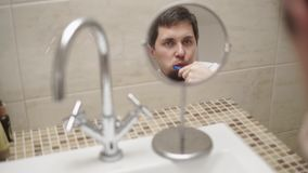 Αντανάκλαση των δοντιών βουρτσίσματος ατόμων σε έναν μικρό στρογγυλό καθρέφτη washroom απόθεμα βίντεο