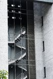Αντανάκλαση των σκαλοπατιών έκτακτης ανάγκης στο γυαλί ενός σύγχρονου κτηρίου με τους γκρίζους τοίχους τσιμέντου στοκ εικόνες