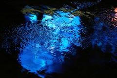 Αντανάκλαση χρώματος στην άσφαλτο μετά από τη βροχή το βράδυ στοκ εικόνες