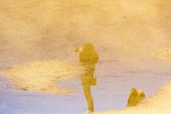 Αντανάκλαση λακκούβας του θηλυκού φωτογράφου στοκ φωτογραφία
