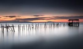 Αντανάκλαση από ένα ηλιοβασίλεμα σε μια αρχαία αποβάθρα αλιείας σε Carrasqueira Στοκ Εικόνες