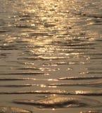 Αντανάκλαση ενός ηλιοβασιλέματος στην άκρη του αμμώδους νερού Στοκ Εικόνες