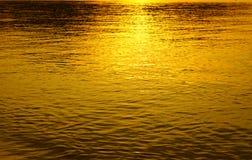 Αντανάκλαση ηλιοβασιλέματος στο χρυσό νερού lite Στοκ Εικόνες