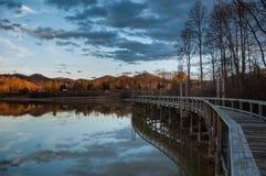 Αντανάκλαση λιμνών στο ηλιοβασίλεμα με την πορεία ποδιών αποβαθρών αποβαθρών Στοκ Φωτογραφία