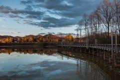 Αντανάκλαση λιμνών στο ηλιοβασίλεμα με την πορεία ποδιών αποβαθρών αποβαθρών Στοκ Εικόνες
