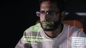 Αντανάκλαση κώδικα στοιχείων στο πρόσωπο προγραμματιστών Χάκερ στα γυαλιά που χαράσσουν programm τον κώδικα τη νύχτα