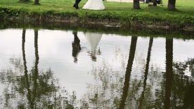 Αντανάκλαση της νύφης και του νεόνυμφου στο νερό φιλμ μικρού μήκους