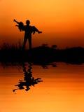 Αντανάκλαση της σκιαγραφίας αγάπης ανδρών και γυναικών στο ηλιοβασίλεμα στοκ εικόνες